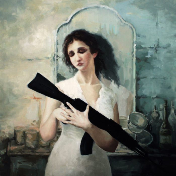 Woman holding an AK rifle in front of a dressing table with mirror