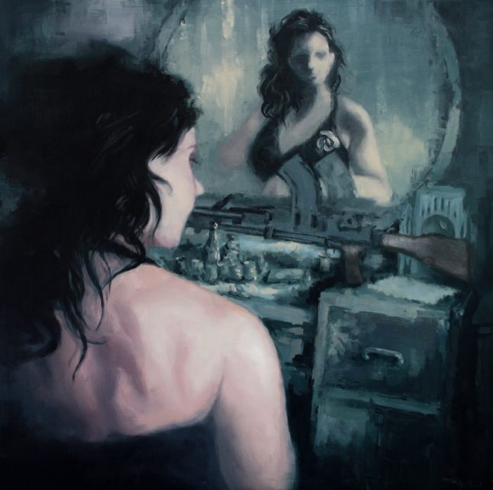 Woman in the boudoir looking in a mirror with a machine gun on the dressing table