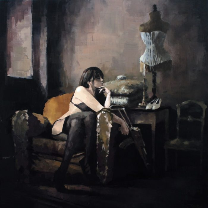 Woman sitting in a couch holding an AK rifle in a dark boudoir room